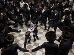 Ultra-Orthodox Jews dance with religious Torah scrolls inside a synagogue in the Mea Shearim neighborhood in Jerusalem.