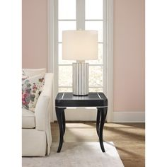 The Flirt end table is all about shape and form. Sleek black finish punctuated with a mother of pearl outline and flourishes at the corners.