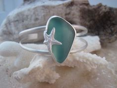 A beautiful chunk of genuine, surf tumbled deep aqua sea glass cuff. You will see this stunning color in many of my pieces although it is becoming rare, I just love to use it as much as possible. I bezel set this large piece in fine and sterling silver and added a starfish because you can never have too much beach! I brushed the whole piece to give it a final soft satin finish. The glass is aprox 1 1/4 long. Slightly asjustable and fits a small to medium wrist. All items arrive gift boxe...