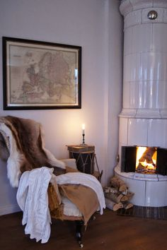 Lovely chair with animal hide throw by this cosy fire. Cozy Nook, Cozy Corner, Cozy Cabin, Hygge, Herd, Scandinavian Style, Scandinavian Cottage, Inspired Homes, Warm And Cozy