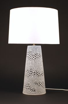 An earthy and contemporary lighting solution turned out in crisp white for an instant touch of clean brightness. A tapered, cylindrical silhouette is embellished with freeform rows of various-sized holes and a tailored seam detail created by the lamp's cord.