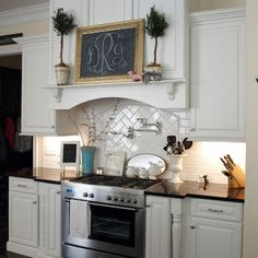 Chalkboard with monogram on ledge above stove