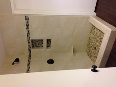 New shower tile. Sea glass mosaic tile accent and pebble floor.
