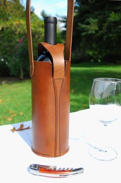 This unique hand-built all-leather wine bottle tote is the classiest way to carry your favorite bottle of vino to parties, events or to bring