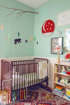 "Jenny Lind Crib from Amazon, woodland mobile from ""Yellow Owl Little Prints"" and remnant of a Singapore flag in an embroidery hoop"