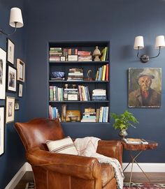 The owner of this California home turned a 15-foot-wide section of hallway into a snug spot for reading with the help of Farrow & Ball's Hague Blue paint and an antique tobacco leather club chair. For a personal touch, she hung family photos in mismatched frames.   - CountryLiving.com