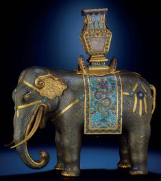 A MAGNIFICENT CLOISONNE ENAMEL ELEPHANT QIANLONG PERIOD The olive green body is inlaid with wavy gilded cloisons representing the wrinkled hide. The back is adorned with a saddle and draped with a blanket enamelled with a lively upright five-clawed dragon, poised to capture a 'flaming pearl' floating amidst ruyi clouds, above crested waves breaking against jagged rocks on a blue ground.