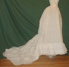 Majestic 1870-1880 Long Trained Petticoat Museum De-accessioned  An exceptional 1870-1880 bustle petticoat that has recently been de-accessioned from a major new York City museum collection.  It is made of lightweight cotton and lavishly trimmed with Val lace.  The petticoat has a long back train that has a center medallion of lace.  It has a drawstring back to help create the bustle effect.  The petticoat is being displayed over an 1870 hoop cage that is being offered in a separate auction.