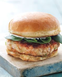 Salmon Burger with Baby Spinach:  2 hamburger buns   1 can (7.5 ounces) salmon, drained and flaked   1/2 celery stalk, finely chopped (2 tablespoons)   1/2 shallot, finely chopped (1 tablespoon)   1 tablespoon mayonnaise, plus more for serving   Coarse salt and ground pepper   2 teaspoons extra-virgin olive oil   Baby spinach, for serving