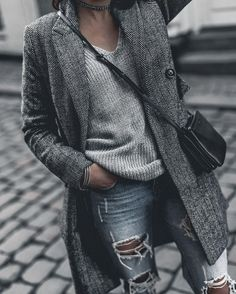 Monja W is in a grey overcoat, over a gorgeous knitted V neck and heavily ripped denim jeans. She wears this look with a glittery choker and a leather handbag. Coat: Superdry. Spring Looks.