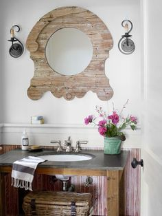 A mirror framed in reclaimed Azobe wood makes a statement in this powder room. #decorating