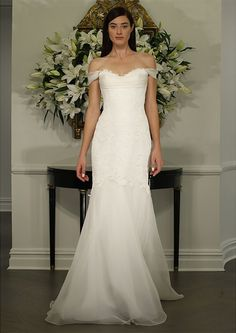 Gown made of Point d'Esprit lace, features a scallop sweetheart neckline with a draped off-the-shoulder silk organza detail and a softly fluted skirt made of silk organza.