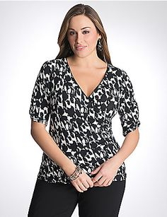 Flaunt your femininity in this gorgeous two-tone floral tee with an amazingly-flattering surplice neckline and ruched elbow-length sleeves. Easy to dress up or down, this versatile top is sure to please. lanebryant.com