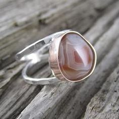 Abeautifully patterned stone is wrapped in a luxe rose gold setting and set on our signature textured sterling silver double band.This ring is sure to be a new favorite piece in your jewelry box! Wear a piece of our region's geographical historywith this double banded sterling silver ring with our hand selected Lake Superior agate. The Lake Superior Agate isnoted for its rich red, orange, and yellow coloring caused by the oxidation of iron.The agate is found throughoutMinnesota…