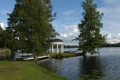 Gazebo next to water and trees.