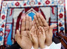 Kolkata, India: A Muslim father assists his son during Eid al-Adha prayers