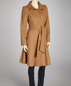 Fashioned from a cozy wool-blend, this coat promises to keep the chilly out and the cozy in. Its elegant styling features an A-line silhouette and a belted sash that falls from the waist.