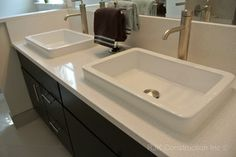 Blanco Maple Silestone counter with white sinks and dark cabinets.