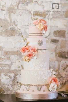 Vintage peachy pink and gold wedding cake with lace and flowers