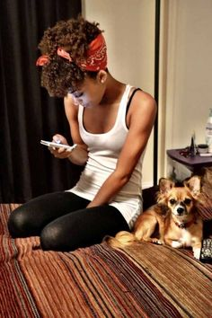Love this - pretty black girl natural 'fro and scarf updo, texting with little dog beside her.