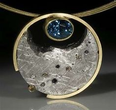 Blue Moon Pendant. Black, white, and champagne diamonds set into Gibeon Meteorite, with a 4.83 ct blue zircon. Surrounded in 18k gold, Jacob Albee,