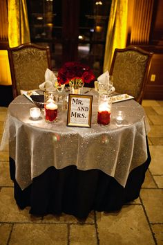 Sparkly silver and black linens with red roses and a Mr. & Mrs. sign at the head of the table | Jillian Ryan Photography | villasiena.cc