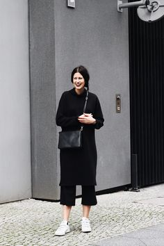 Elisa from the Fashion- and Lifestyleblog www.schwarzersamt.com shows a minimalistic autumn winter look in allblack with white sneakers. She is wearing a longdress with a high neck from MONKI, a black culotte from TOPSHOP, white stan smith sneaker from ADIDAS and a black celine lookalike from C&A. It's a straight and minimal allblack outfit in layering look.