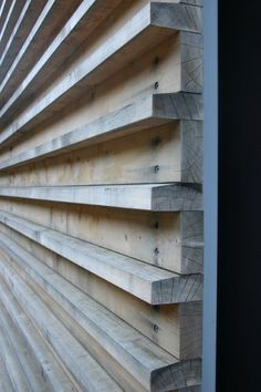 these wood slats are utilitarian in the way they are connected to the substrate — countersunk screws — but note the care in angling the top of the projecting pieces, so water sheds off the wood.