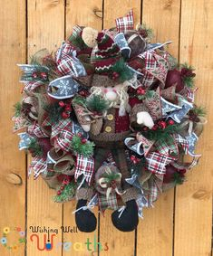 """This beautiful rustic Santa wreath has a base of moss green, muted red and brown burlap these colors match the Santa doll found in the center of the wreath. This Santa wreath has a fun Farmhouse Christmas feel with ribbons of grey snowy snowflakes, a red brown and black plaid, and a country ribbon saying """"Merry Christmas"""" ! This Wreath would look perfect with any of your santa decor especially if you're a fan of the rustic Farmhouse theme."""
