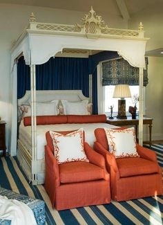 Chinoiserie canopy bed with lovely arm chairs for seating at the end of the bed.