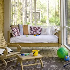 Laid-Back Porch - An extra-deep swing makes lazy Sunday afternoons on this porch a must.  Small pops of subdued color provide a beach-like atmosphere.