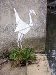 A new Banksy piece popped up yesterday in the UK featuring an adeptly stenciled origami crane snagging a goldfish from a small canal. While the work has yet to appear on the artist's website for positive verification, Street Art News seems to think it's the real deal. Photos by the lonely villein.