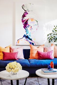 White living space with a bright blue sofa, and modern artwork