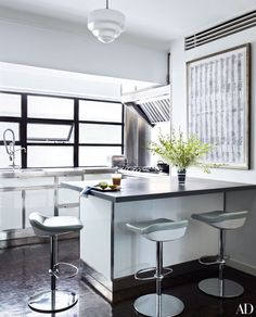 In this Hong Kong kitchen, bar stools flank a small island, providing extra room for accessories designer Fiona Kotur and her young family to gather around for breakfast or a quick snack. | archdigest.com