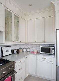 Gorgeous kitchen features ivory cabinets paired with Silestone Lagoon countertops in a suede finish and a white subway tiled backsplash on upper part of walls.