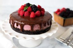Colorful Pressure Cooker Raspberry Cheesecake with an Oreo cookie crust, dripping with rich chocolate ganache and crowned with berries.