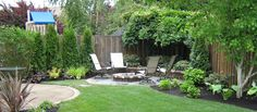 Cozy backyard surrounded with wooden fence and range chairs
