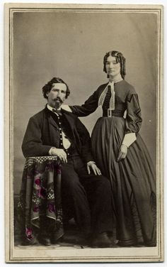 Carte de visite by W. Wykes of Grand Rapids, Mich. A man wearing civilian clothes and a military-style vest complete with brass buttons sits in a chair and rests his right forearm on an need table covered by a tablecloth. The woman standing to his left, presumably his wife, rests her right hand upon his shoulder. Her hair is formed in tight ringlets. This image may not be reproduced by any means without permission.