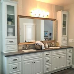 A large white vanity with double sinks provides plenty of space for two in this transitional master bathroom. Two tall white cabinets flank the mirror for additional storage space.