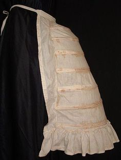 """1885 Bustle  A long bustle made out of white cotton. The fullness of the bustle is adjustable by the lacing on the inside of the bustle, which controls each of the 8 watchspring ribs located down the back. Features flounce on the end of the bustle for extra fullness.  The waist fastens with ties and would fit up to a 36"""" waist. In lovely strong condition with two places where period repairs have been made on the right side to the end of the bone channel and two moth holes on the bottom…"""