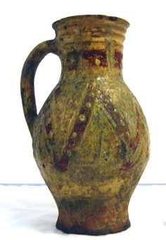 London-type ware. Pottery baluster jug; yellow-green glaze, band of brown round neck & brown zigzag on body with yellow-green pads; rod handle; Rouen-style decoration.