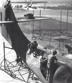 Repairs and maintenance at base. Note PBY in background headed down ramp going out on another mission