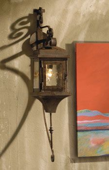 Grand Hacienda Lantern    Item # 5312  Our spectacular, oversized, hand-forged iron lantern is adapted from Spanish colonial wall sconces of old. Its elaborate design with scrolled arm, seeded glass panes, and chain-closure door evokes memories of days gone by. Outdoor safe design has a stained and sealed finish that beautifully withstands the elements.