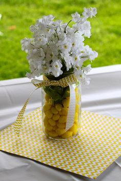 """Table centerpieces for """"You Are My Sunshine"""" first birthday party: flowers in mason jars, filled with lemon drops."""