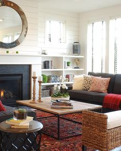like the whole room and the fireplace with the brick being black, oriental rug, daybed in living room, rustic coffee table
