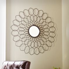The Upton Home Gia spiro mirrored wall sculpture adds style by a matte black frame and circular beveled mirror. Metal waves wind into a geometrical pattern to add interest to your empty wall space. Displaying this piece is as simple as hook and hang!