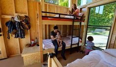 This July 24, 2014 photo released by California State Parks shows Cal Poly Pomona Architecture students Emily Williams, top, and Bryan Charney as they pose for photos with children in a cabin called The Wedge, one of four designs that Parks Forward proposes to put on hundreds of campsites throughout the California State Parks system, displayed at the State Fair Exhibit in Sacramento, Calif. Parks Forward, a group formed by the state to help revamp California's state parks, wants to open up…