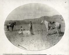 Con Jackson (who won the bronc riding contest at the Cattlemen's Convention in Wichita in 1901) earmarking a yearling while Lee Larrabee applies the branding iron, near Arkalon in Seward County.