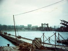 Vehicle of the 7th Army cross the Rhine River from Ludwigshafen to Mannehim over the Ger Davidson Bridge, under cover of smoke screen. In the background is the wreckage of the Ludwigshafen railway bridge, destroyed by the retreating Germans. Ludwigshafen, Germany - March 1945