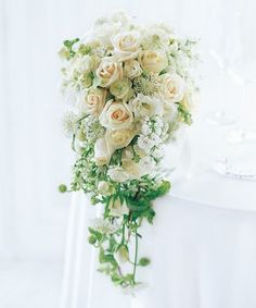 A soft and beautiful romance lies within this soft cascading bouquet made up of cream roses, spray roses, white lilac, blue and white lace flower, lisianthus and hedera.